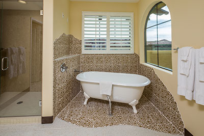 bathroom inside guest room at Cibola Vista resort with clawfoot tub and shower with glass door