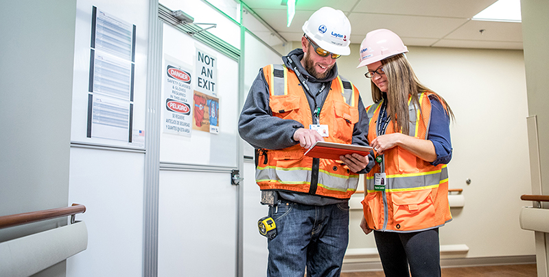 Man and woman working in the field, reviewing plans on an iPad